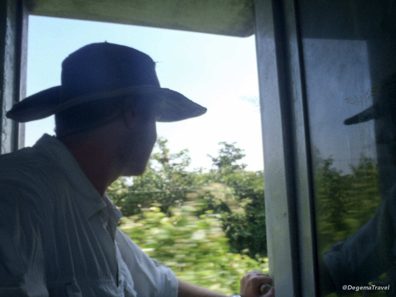 Riding in the open door of a moving train near Kanchanaburi, Thailand