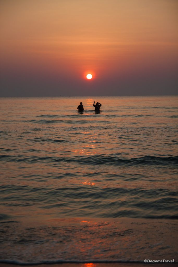 Couple playing in the sea at dawn on Hua Hin Beach, Thailand